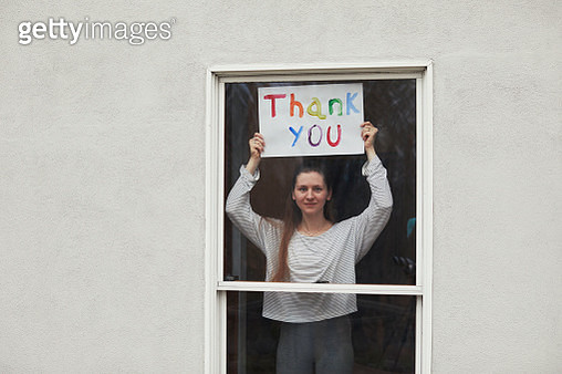 Young women holding up Thank You sign in window looking out - gettyimageskorea