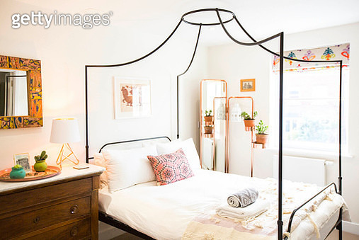Interior Of A Stylish Modern Bedroom Based In Canterbury, Kent. The Bedroom Features A Double Four Poster Bed, A Large Copper Mirror, Indoor Plants, Hints Of Antique, With A Wooden And Marble Chest Of Drawers And Brightly Colored Furnishings - gettyimageskorea