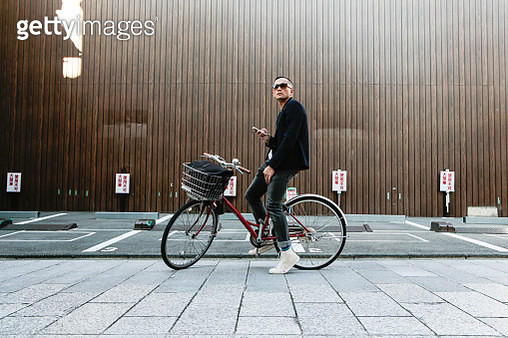 A tourist in his bicycle​ stops in front of a parking lot to check his mobile device for directions in an inner street in Kyoto, Japan. - gettyimageskorea