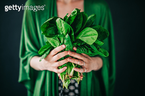 Young woman holding spinach leafs salad - gettyimageskorea