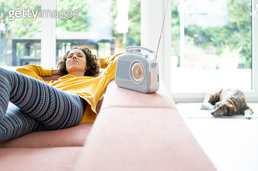 Woman lying on couch listening to music with portable radio at home - gettyimageskorea