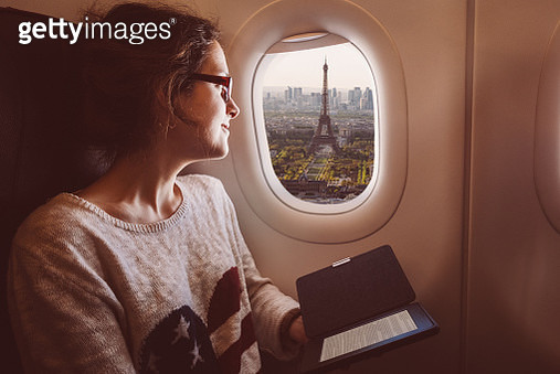 Smiling woman enjoying Paris from the airplane window - gettyimageskorea