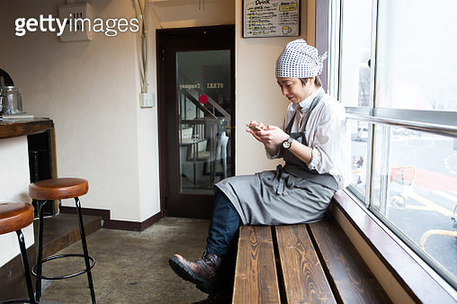 The female manager sits on the chair in the store and updates the SNS. - gettyimageskorea