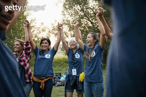 Volunteers holding hands and cheering in park - gettyimageskorea