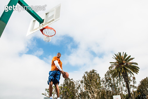 Young man jumping to score hoop in basketball - gettyimageskorea