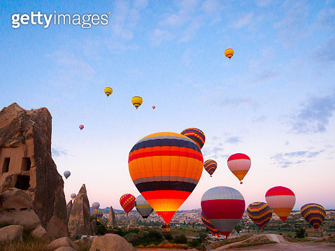Hot air balloons taking off at dawn from amid rock 'fairy chimneys'  near Goreme, Cappadocia, Turkey. Hot air ballooning is an extremely popular tourist activity in this region. - gettyimageskorea