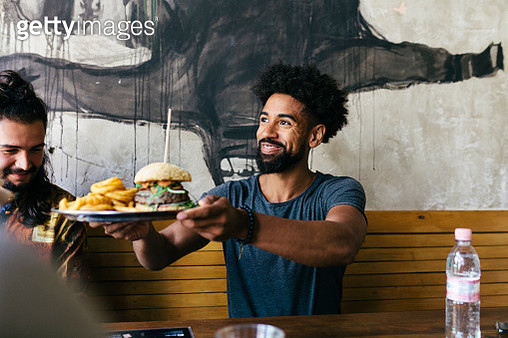 A customer smiling as he receives his food at a trendy burger restaurant. - gettyimageskorea