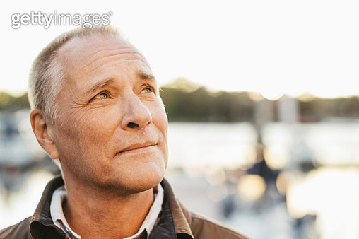 Thoughtful senior man looking up outdoors - gettyimageskorea