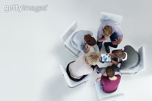 High angle view of businesspeople using digital tablet together in office - gettyimageskorea