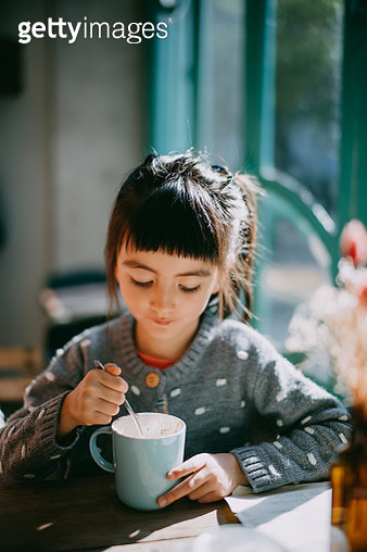 Young mixed race girl having hot chocolate in cafe - gettyimageskorea