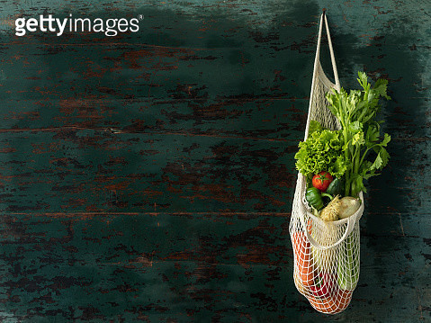 Market fresh salad vegetables hanging in a reusable string cotton bag, on an old wood turquoise colored wall background. - gettyimageskorea