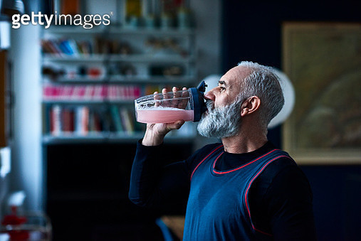 Side view portrait of active man in his 50s drinking pink liquid fruit juice, head and shoulders, grey hair and beard, back from morning run, recovering, thirsty - gettyimageskorea