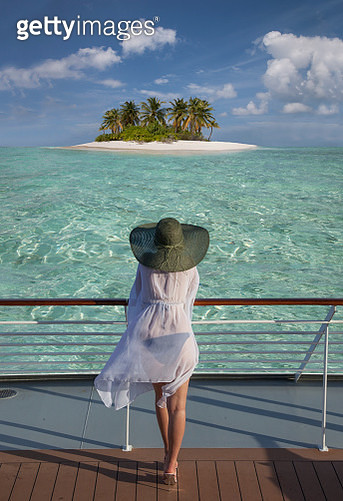 A young woman on the deck of a cruising ship watching a small island with white sands and coconut palms. - gettyimageskorea