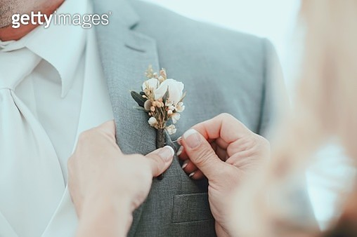 Cropped Image Of Hands Putting Boutonniere On Bridegroom Suit - gettyimageskorea