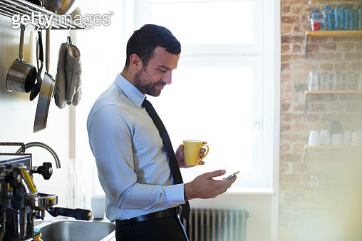 Businessman having coffee break in office kitchen looking at cell phone - gettyimageskorea