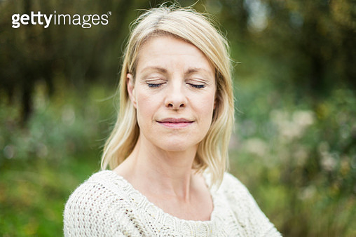 Portrait of blond woman with eyes closed outdoors - gettyimageskorea