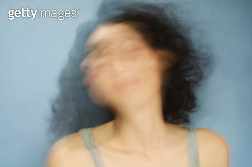 Blurred Motion Of Young Woman Against Blue Background - gettyimageskorea