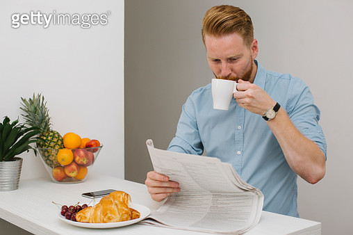 Businessman drinking coffee while reading newspaper in the morning at home - gettyimageskorea