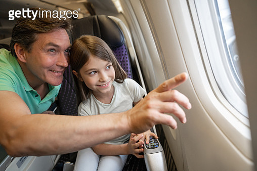 Happy father and daughter traveling by plane and looking through the window - gettyimageskorea