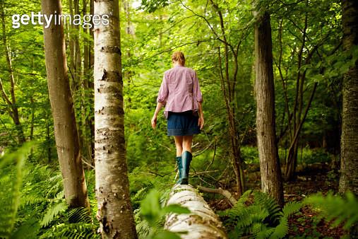 A woman in wellingtons walking along a fallen tree trunk,in woodland. - gettyimageskorea