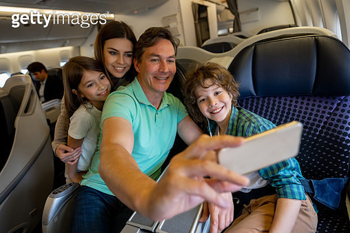 Happy family traveling by plane and taking a selfie - gettyimageskorea