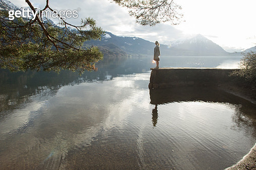 Woman pauses at end of mountain lake wall, looks off - gettyimageskorea
