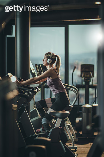 Female athlete listening music while practicing on exercising bike in a health club. - gettyimageskorea