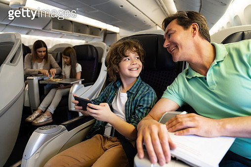 Happy father and son traveling by plane and using a cell phone onboard - gettyimageskorea