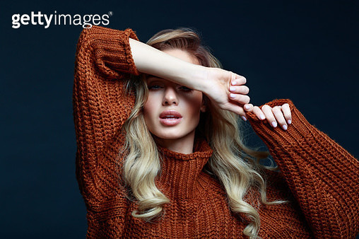 Fashion portrait of long hair blond young woman wearing brown sweater, smiling with raised hands. Studio shot against black background. - gettyimageskorea