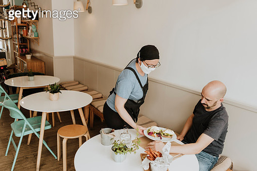 Waitress with protective mask serving food in a coffee shop - gettyimageskorea