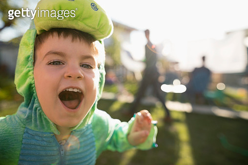 Close up playful, cute toddler boy wearing dinosaur costume, gesturing fiercely in backyard - gettyimageskorea