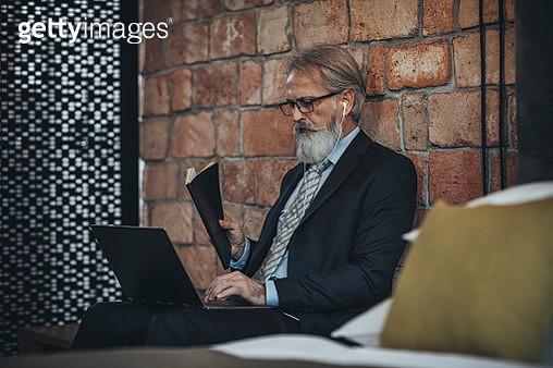 Businessman looking at laptop in hotel room - gettyimageskorea