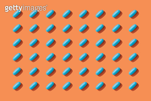 Repeated Pills on Orange Color Background - gettyimageskorea