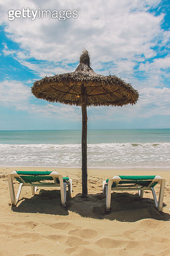 Thatched Parasol And Lounge Chairs On Beach Against Cloudy Sky - gettyimageskorea