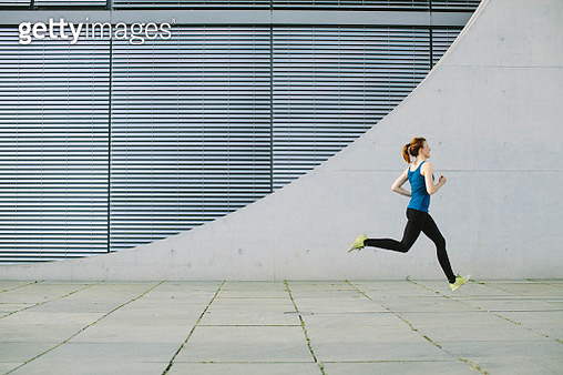 Young woman running strides in front of a modern building - gettyimageskorea