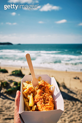 POV hand holding a box of Fish and Chips above Fistral Beach, Newquay, Cornwall on a sunny September day. - gettyimageskorea