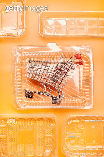 Shopping cart in plastic packaging on orange colored background - gettyimageskorea