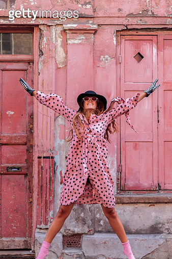 Model In Pink Polka Dot Dress And Gloves With Black Hat In London Jumping Of Happiness - gettyimageskorea