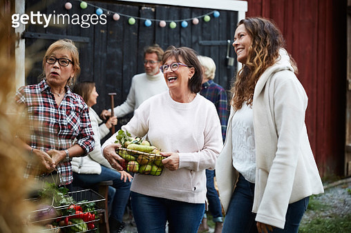 Cheerful women standing with baskets against friends at farm during dinner party - gettyimageskorea