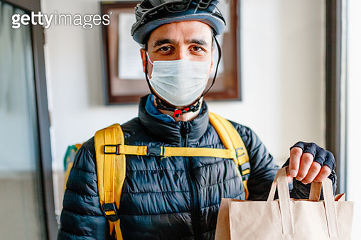 Young man as a courier delivering  food - gettyimageskorea