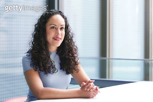 Portrait of a LatinX woman with curly hair, looking away, wears a light blue top in an office setting. - gettyimageskorea