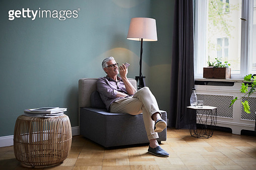 Mature man using cell phone at home - gettyimageskorea