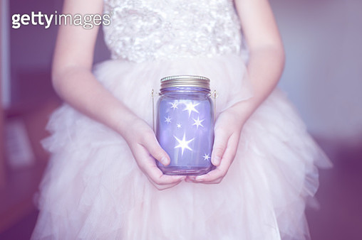 Girl's hands holding a glass jar full of stars - gettyimageskorea