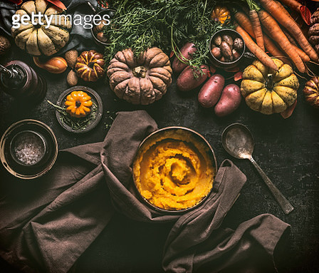 Mashed pumpkin in cooking pot with spoon and ingredients on rustic kitchen table - gettyimageskorea