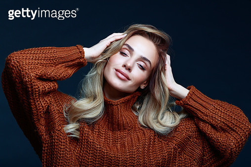 Fashion portrait of long hair blond young woman wearing brown sweater, smiling with eyes closed and raised hands. Studio shot against black background. - gettyimageskorea