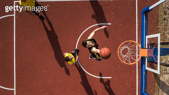Basketball player scoring with slam dunk, drone point of view, outdoor - gettyimageskorea