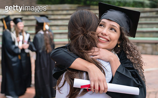 Portrait of a happy student hugging her mother and celebrating her graduation - education concepts - gettyimageskorea
