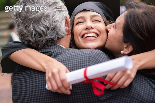 Portrait of a couple of proud parents hugging their daughter and celebrating her graduation - education concepts - gettyimageskorea