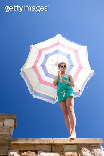 Woman in sunglasses holding beach umbrella - gettyimageskorea