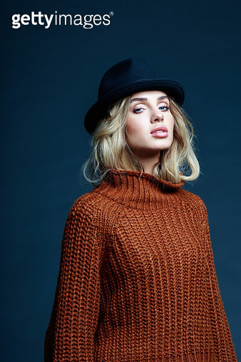 Fashion portrait of long hair blond young woman wearing brown sweater and black hat, looking at camera. Studio shot against black background. - gettyimageskorea